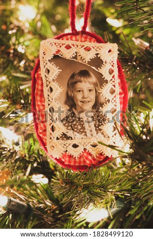 A vintage handmade Christmas photo ornament. The frame is made of red and white gingham fabric; lace ribbon frames the photo. Circa 1980. A vintage photo filter was used to further enhance the effect.