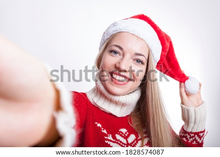 selfie taken by a blond woman in xmas mood wearing a santa hat. she took a picture of herself with her mobile while holding bobble. special christmas greeting profile avatar of cheerful young lady