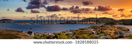 Aerial panoramic view of a small town on the Atlantic Ocean Coast. Dramatic Colorful Twilight Sky. Sunset or Sunrise. Taken in Trinity, Newfoundland and Labrador, Canada. #1828588025