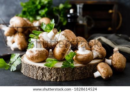 Raw mushrooms champignons on black background, cooking fresh champignons Royalty-Free Stock Photo #1828614524