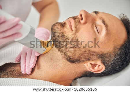 Female esthetician hands in sterile gloves removing unwanted hair from male neck with laser device Royalty-Free Stock Photo #1828655186