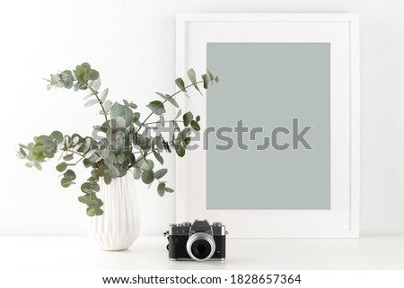 Bouquet of eucalyptus in the ceramic vase, camera and empty picture frame on the table against grey wall, minimalist interior design