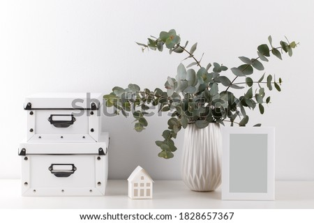 Bouquet of eucalyptus in the ceramic vase, empty picture frame on the table against white wall, minimalist interior design
