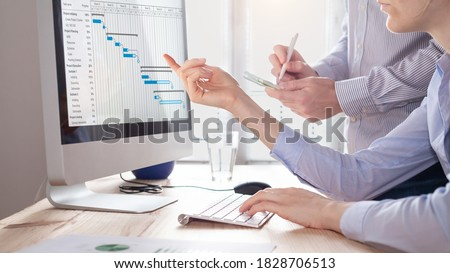 Project management team updating planning schedule with Gantt chart on computer at the office to communicate on task progress and plan the next deliverables. Program manager and assistant discussing Royalty-Free Stock Photo #1828706513
