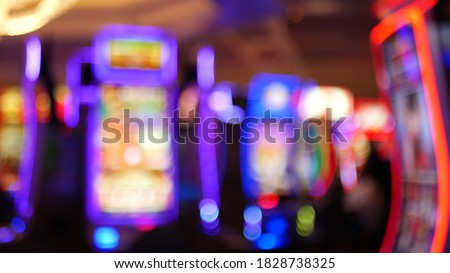 Defocused slot machines glow in casino on fabulous Las Vegas Strip, USA. Blurred gambling jackpot slots in hotel near Fremont street. Illuminated neon fruit machine for risk money playing and betting. Royalty-Free Stock Photo #1828738325