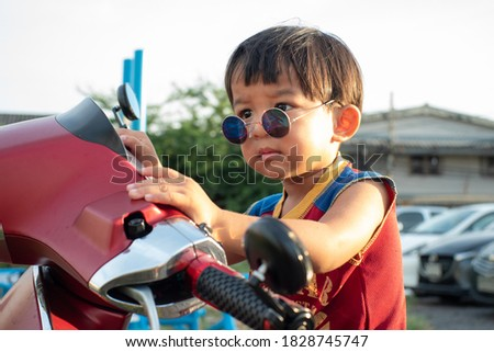 Little smart boy wear sunglasses sitting on vintage scooter motorcycle outdoor portrait Royalty-Free Stock Photo #1828745747