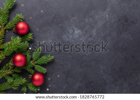Christmas background with fir tree and red balls on dark stone background. Top view Copy space - Image