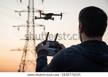 Man operating drone close to the electrical wire/ man holding remote control drones / drone controller. Drone safety. Man operating drone / man holding remote control drones. #1828776035
