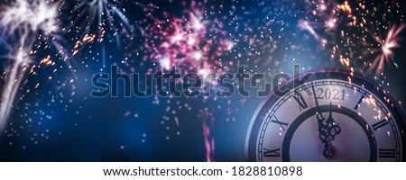 countdown new years eve 2021 with colorful fireworks on dark blue sky background, clock and blurred firecrackers  for happy new year celebration, explosion light effects  #1828810898