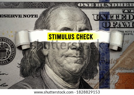 Torn bills revealing Stimulus Check words. Idea for USA check, Coronavirus affects US dollar, people need to spend Royalty-Free Stock Photo #1828829153