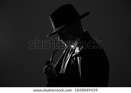 Old fashioned detective with smoking pipe on dark background, black and white effect Royalty-Free Stock Photo #1828849439