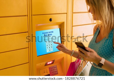 Woman entering code to receive parcel in post locker Royalty-Free Stock Photo #1828876721