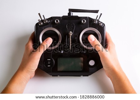 Black remote control panel and hands on controls for drone. Top view on white background. Horizontal orientation. High quality photo