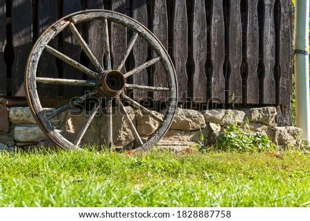 Wooden wagon wheel on a wall #1828887758