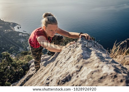 Young strong girl climbs to top of cliff. Overcoming obstacles and courage. Ambitious climber climbing high mountain to achieve success. Royalty-Free Stock Photo #1828926920