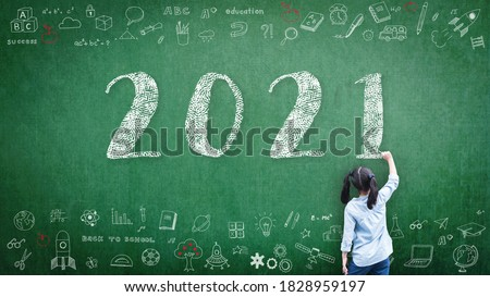 2021 Happy new year school class academic calendar with student kid's hand drawing greeting on teacher's green chalkboard for educational celebration, back to school, STEM education classroom schedule Royalty-Free Stock Photo #1828959197