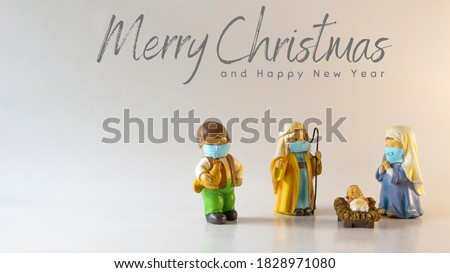 Merry Christmas text with figures of a Bethlehem portal, with Saint Joseph, the Virgin Mary and the baby Jesus with hygienic masks due to the Covid-19 pandemic. Concept New Normal #1828971080