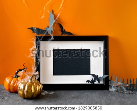 Happy halloween holiday concept. Black frame on orange background. Halloween decorations, pumpkins, bats, black frame. Halloween party greeting card mockup with copy space.