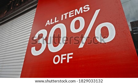 White text on a red banner standing on the street with the inscription 30% off