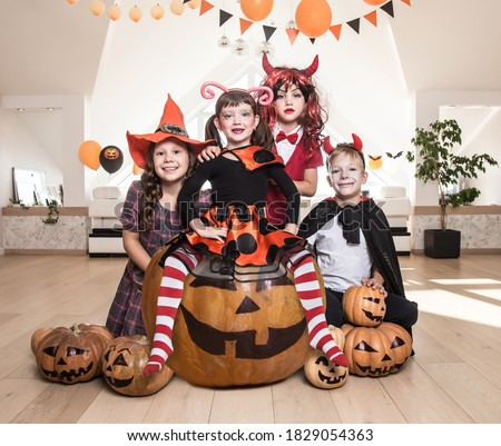 group of funny  children in costume celebrate together a halloween party