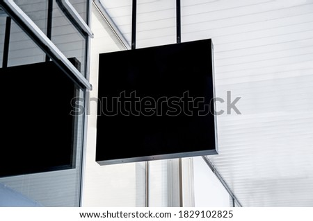 Square black signboard outside store or cafe in the street