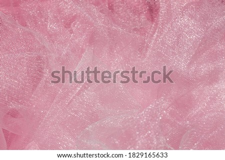 Pink tulle fabric texture top view. Coral background. Fashion color trends feminine tutu skirt flat lay, female blog backdrop for text signs desidgn. Girly abstract wallpaper, textile surface.