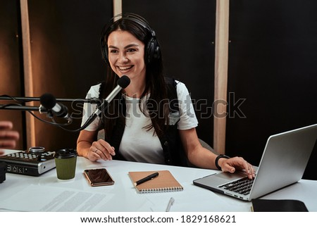 Portait of attractive young female radio host speaking in microphone while moderating a live show