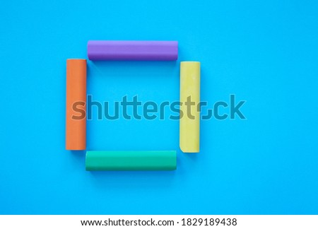 Square made from colorful chalk sticks isolated on blue background; close up of chalks in various colors; children's stationery; creativity material; picture frame; flat lay, top view, copy space