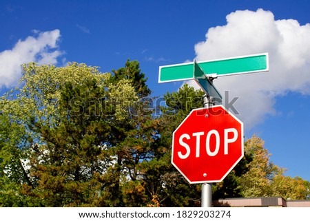 Real metal Red Stop sign with two green blank road street name signs post, blue sky, white clouds, and green trees background.