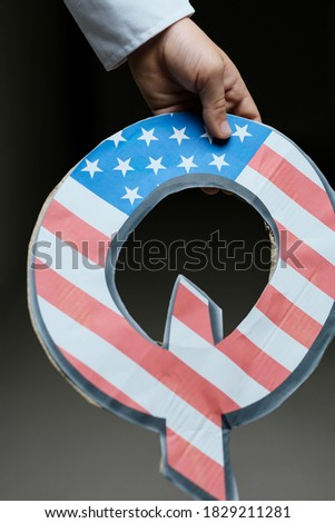 QAnon concept image. Q-Anon movement in the United states. Unrecognisable child's hand holding Q letter with american flag. Selective focus. Royalty-Free Stock Photo #1829211281