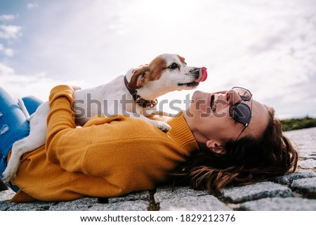 A beautiful woman laughing while her pet is licking her face in a sunny day in the park in Madrid. The dog is on its owner between her hands. Family dog outdoor lifestyle Royalty-Free Stock Photo #1829212376