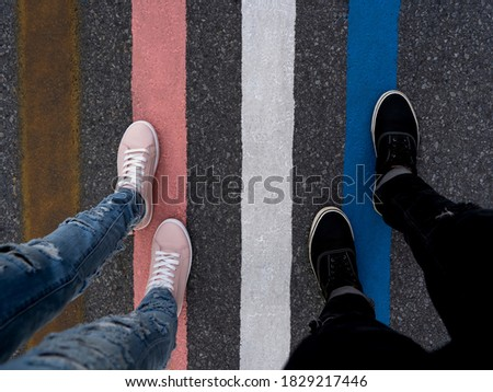 Two people walking on colored stripes on the asphalt of the street, a woman in pink shoes and a man in black shoes