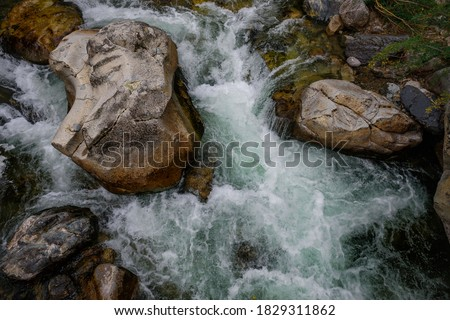 Rapid and powerful water flow between large rocks, close-up. Boulders in cold mountain river. Natural backgrounds. Royalty-Free Stock Photo #1829311862