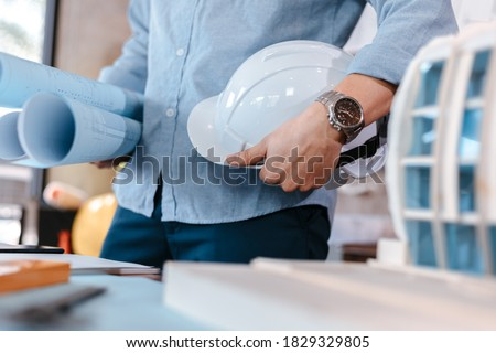 engineer hold engineer drawing design blueprints and safety helmet in room at site construction. Royalty-Free Stock Photo #1829329805