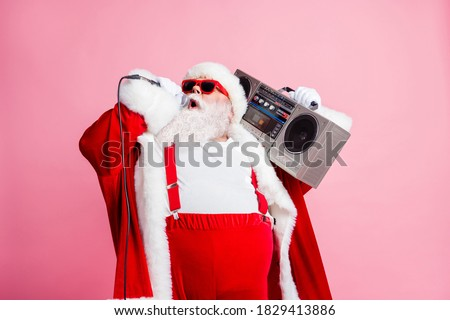 Cool north-pole pop star celebrity white grey hair beard santa claus big abdomen sing x-mas christmas songs hold mic boom box wear suspenders sunglass cap isolated pastel color background