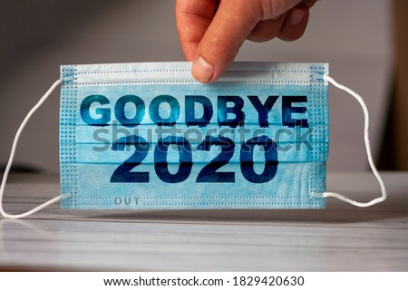 The hand holds a medical and protective mask with the word GOODBYE 2020. Concept of coronavirus quarantine. Prevent or stop the spread of the COVID-19 worldwide. Royalty-Free Stock Photo #1829420630
