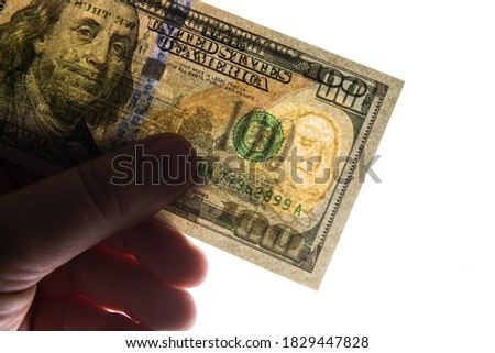 Photographed in this way 100 US dollars in a backlight that two sides of the bill are visible at once, as well as watermarks and protection against forgery