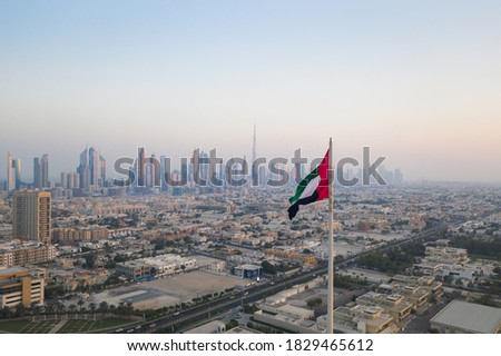 Unique view of UAE, United Arab Emirates national flag waving in the air with Dubai skyline in background during sunset