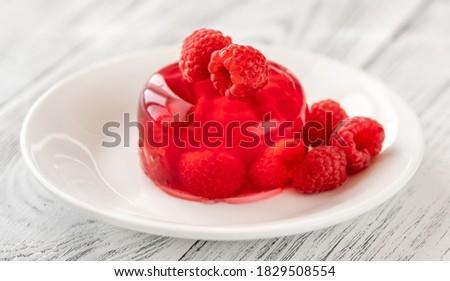Portion of raspberry gelatin dessert on white plate Royalty-Free Stock Photo #1829508554