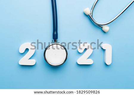 Stethoscope with 2021 number on blue background. Happy New Year for health care and medical banner/calendar cover. Creative idea for new trend in medicine treatment and diagnosis concept. #1829509826