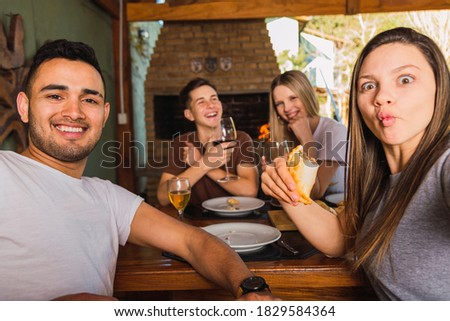 Group of friends eating empanadas.  Young friends eating and toasting.  Couple takes a picture while eating.  Couple makes funny gestures for the camera.  Concept of friendship, food and relaxation.