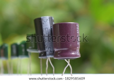 cluster of electric capacitors in blurred background - electronic evolution , electric evolution , capacitor evolution , electronic queue - uF capacitor uf condenser #1829585609