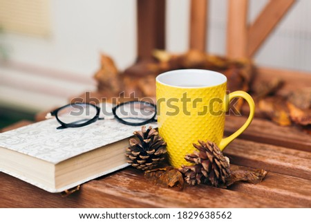 Close up photo of glasses, yellow mug with tea, pine cone, book and orange fallen leaves on wooden table outside. Comfort, coziness and hygge concept. Autumn mood. Still life. Selective focus.