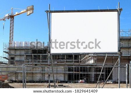 Blank information board near the construction site with a new concrete building among scaffolding #1829641409