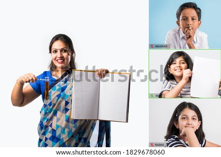 Portrait of Indian lady teacher in saree stands against green, white or blackboard , conducting online class using Camera, internet and lights Royalty-Free Stock Photo #1829678060