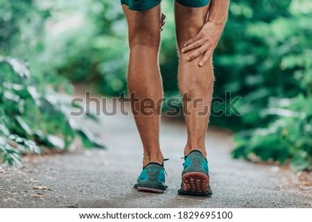 Runner leg injury painful leg. Man massaging sore calf muscles during running training outdoor from pain. Royalty-Free Stock Photo #1829695100