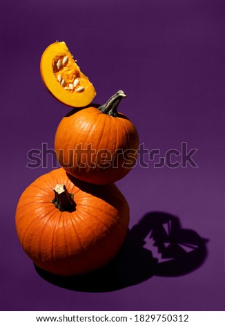 Dark artistic photo of orange pumpkins on purple background. Shadow as Jack head. Balancing vegetables. Halloween concept. Hard light food photography