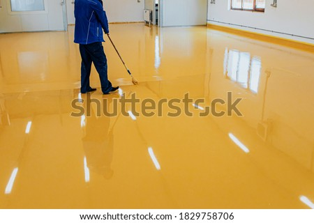 Worker, coating floor with self-leveling epoxy resin in industrial workshop. Royalty-Free Stock Photo #1829758706