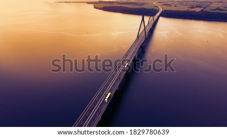 Bridge spanning over a bay with traffic passing in the evening light. Aerial view. Royalty-Free Stock Photo #1829780639