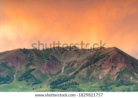 An incredible, warm sunset rises over a mountain peak. The colors apply to both the Fall and Summer seasons